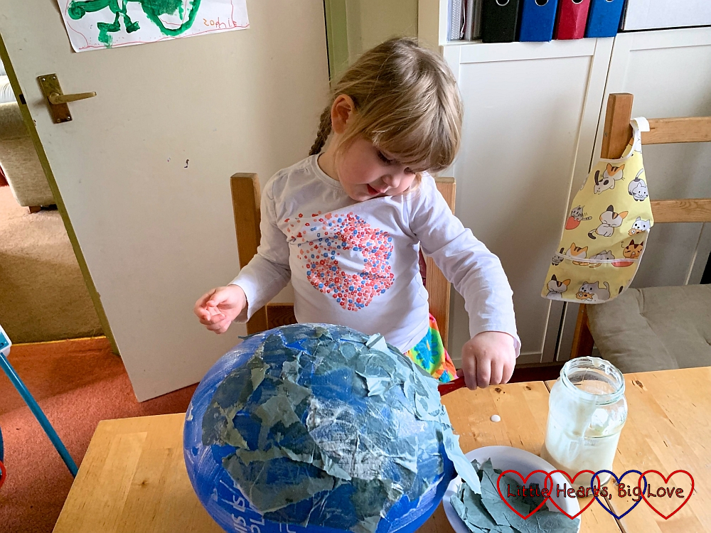 Sophie covering the balloon with pieces of green tissue paper and watered down glue