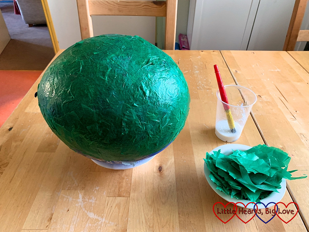 A balloon covered with a layer of green tissue paper papier-mache next to a pot of watered down glue and a bowl full of pieces of green tissue paper
