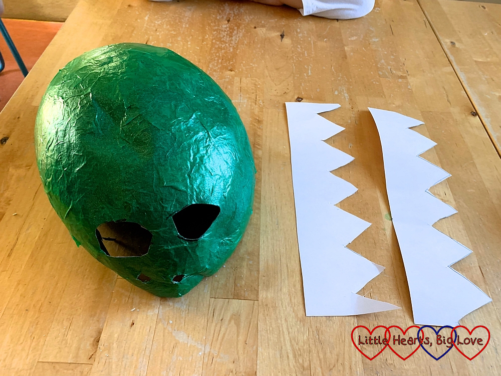 The papier mache dinosaur head with holes cut out for eyes and nostrils next to two pieces of white card with zigzags cut out