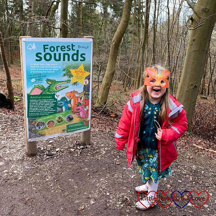 """Sophie wearing a Zog mask and standing next to a """"forest sounds"""" board on the Zog trail"""