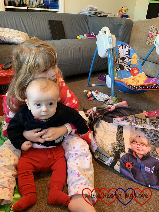 Sophie and Thomas snuggling together to watch CBeebies with Jessica's photo blanket next to them