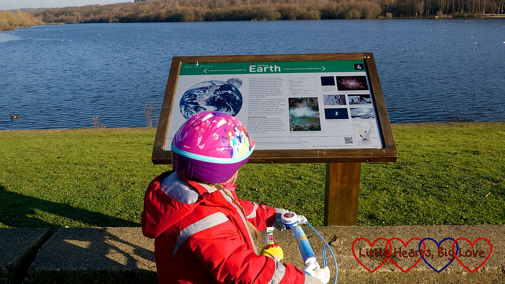 Sophie on her bike looking at the 'Earth' information board