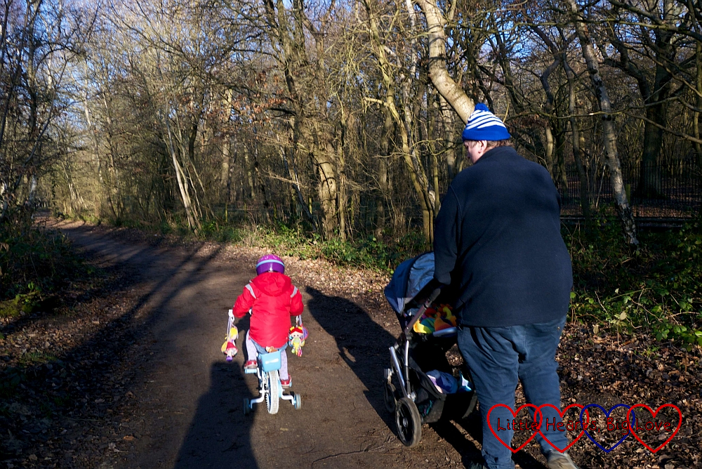 Sophie cycling along the path; Daddy following with Thomas in the buggy
