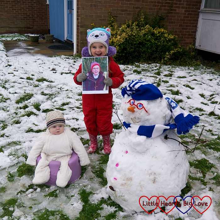 Sophie (holding a picture of Jessica) in the snow with Thomas in the Bumbo and a snowman with pipe-cleaner glasses and a blue and white hat and scarf