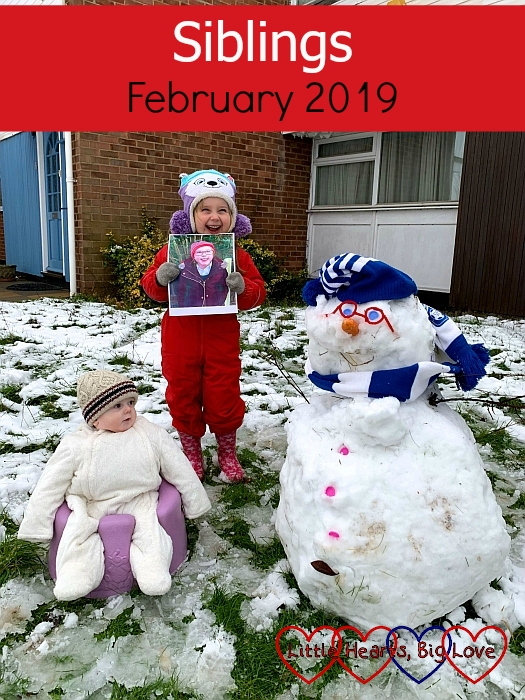 "Sophie (holding a picture of Jessica) in the snow with Thomas in the Bumbo and a snowman with pipe-cleaner glasses and a blue and white hat and scarf - ""Siblings - February 2019"""