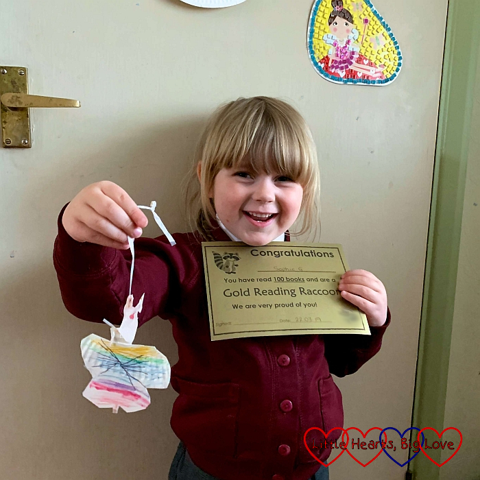 Sophie with her gold Reading Raccoon certificate and a butterfly made by Jessica's friend