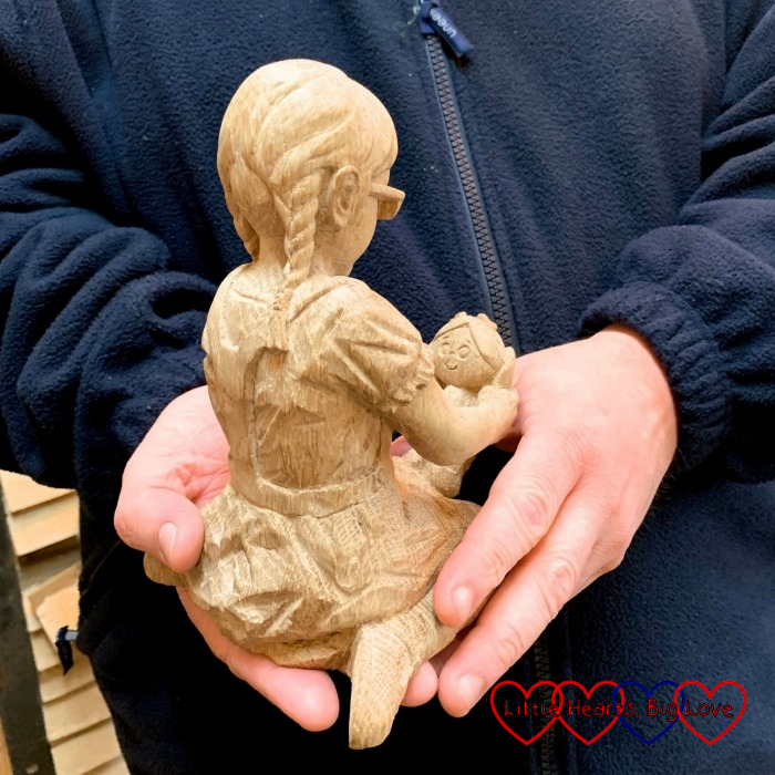 The untreated carving of Jessica holding Kerry viewed from the back