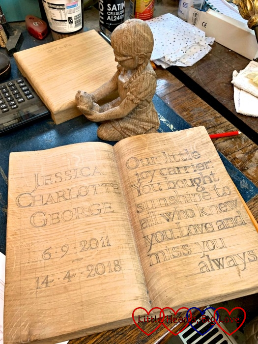 "The carving of Jessica and Kerry on a table with the carved book in front with ""Jessica Charlotte George 6.9.2011 - 14.4.2018. Our little joy carrier. You bought [sic] sunshine to all who knew you. Love and miss you always."" pencilled out"