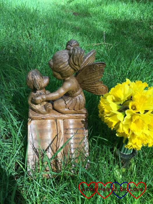 A wooden memorial with a fairy and a teddy bear on top of an open book