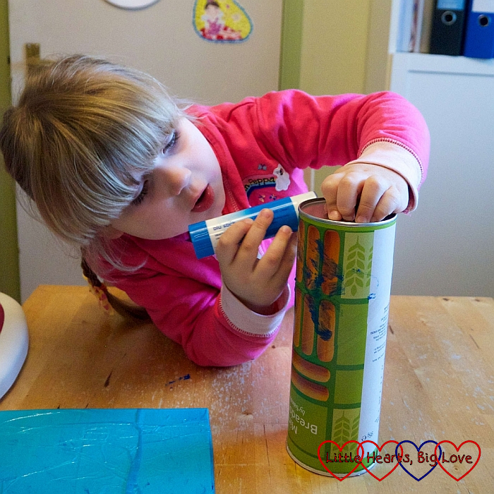 Sophie using a glue-stick to spread glue on the cardboard tube