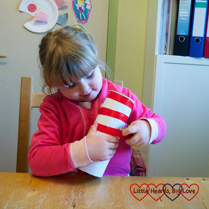 Sophie using red sticky tape to make horizontal stripes on the cardboard tube