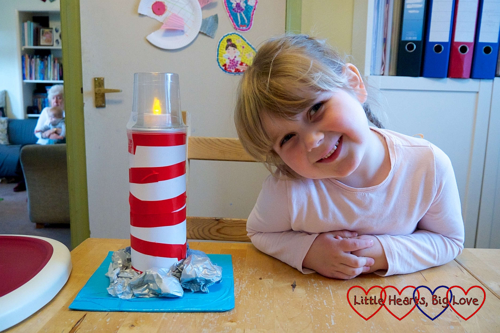 Sophie next to the lighthouse with the tea light and yogurt pot added on top of the cardboard tube