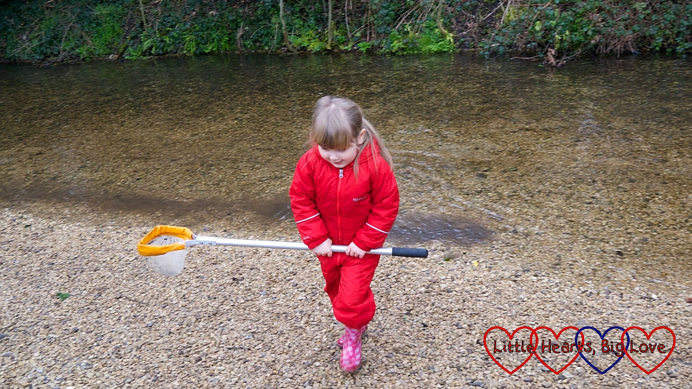 Sophie walking away from the river holding her net
