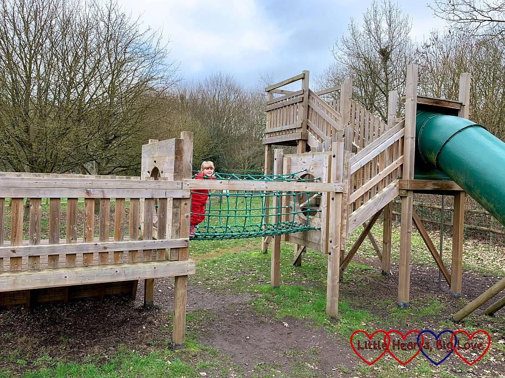 Sophie going across a net bridge in the children's play area