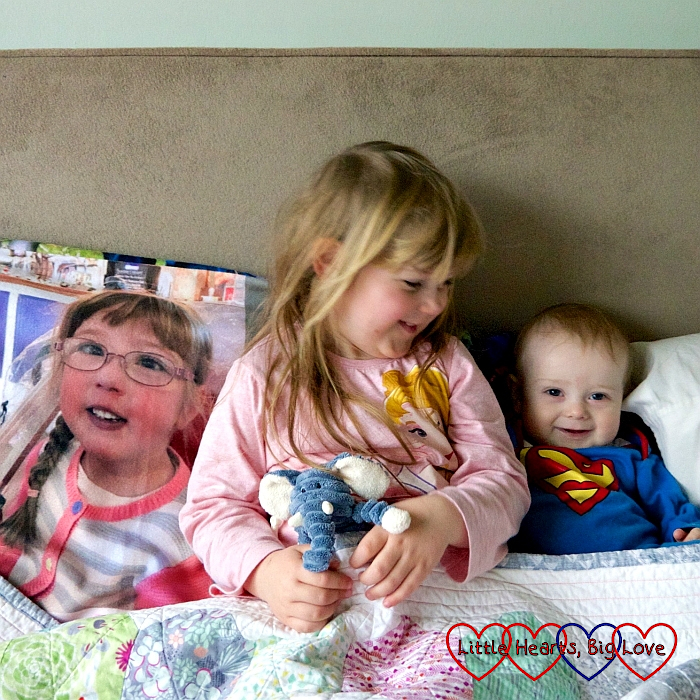 Sophie and Thomas sitting on my bed in their pyjamas next to Jessica's photo blanket