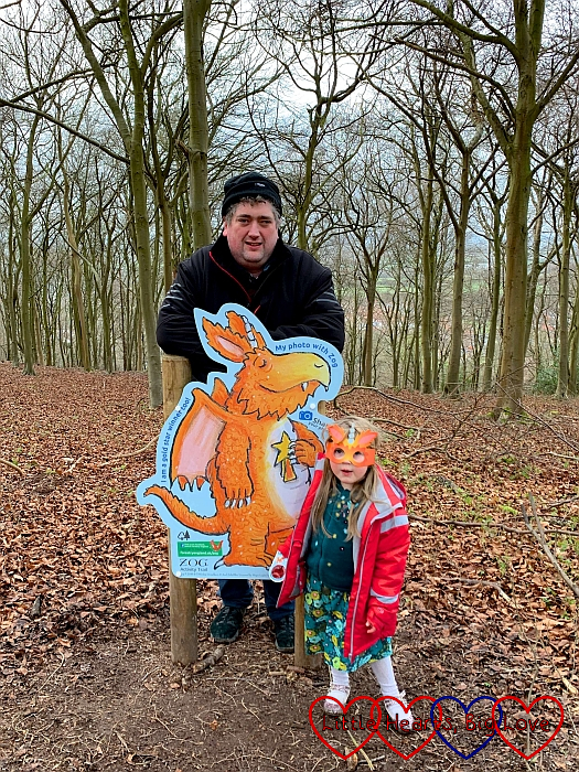 Sophie wearing her Zog mask with Daddy standing next to Zog at the end of the trail