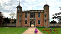 Sophie standing in front of the gate house at Charlecote Park