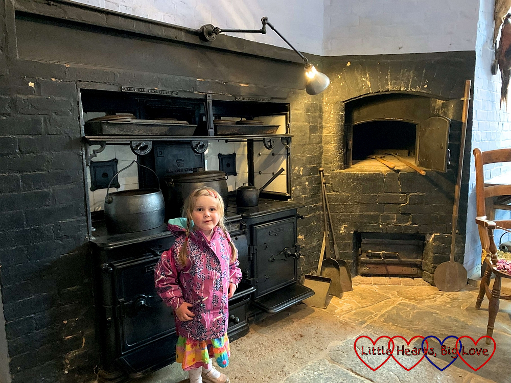 Sophie in front of the range in the Victorian kitchen