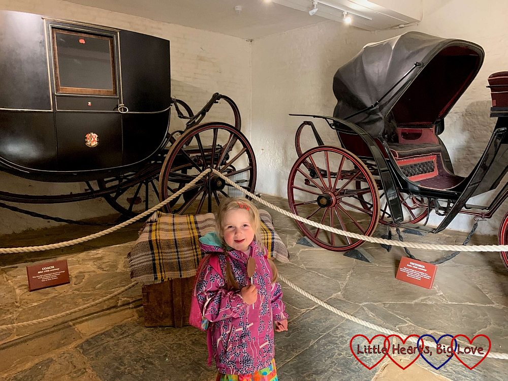 Sophie in front of the carriages in the carriage collection at Charlecote Park