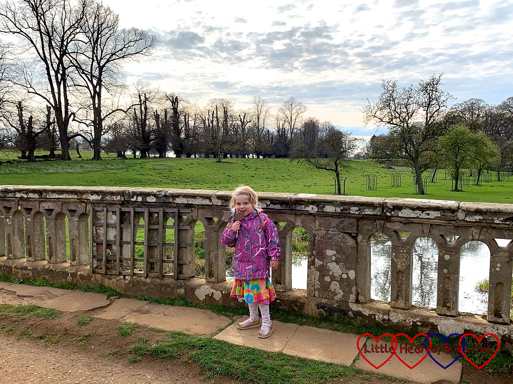 Sophie standing on a stone bridge at Charlecote Park holding a chocolate lolly