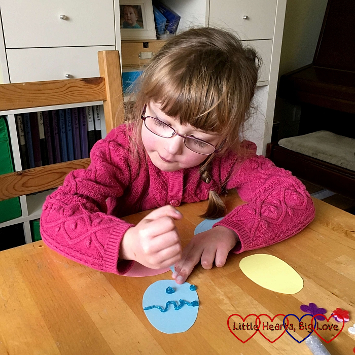 Jessica decorating one of the cardboard egg shapes using glitter glue