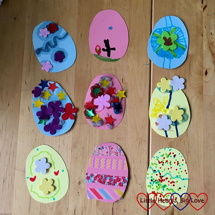 Nine pastel-coloured cardboard eggs, each decorated using pens, stickers, glitter glue and washi tape