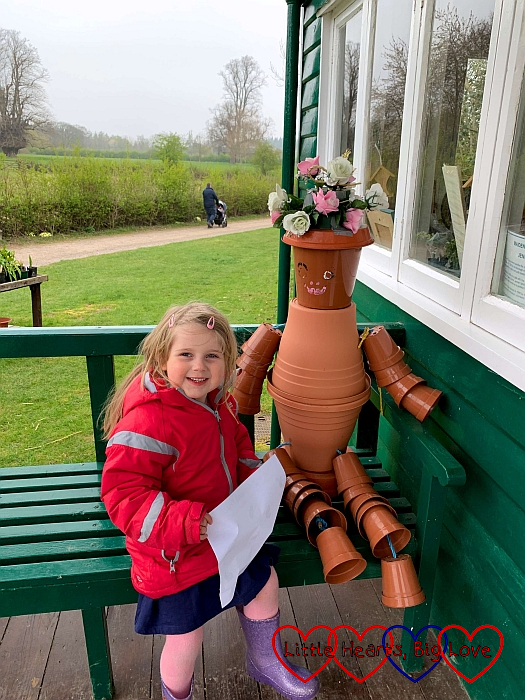 Sophie sitting next to a person made from plant pots at Chiltern Open Air Museum