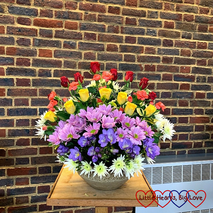 A flower arrangment with the flowers arranged in rainbow colours from back to front