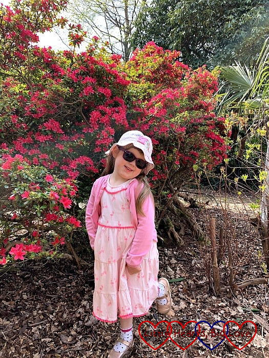 Sophie posing in her hat and sunglasses in front of the rhododendrons at Langley Park