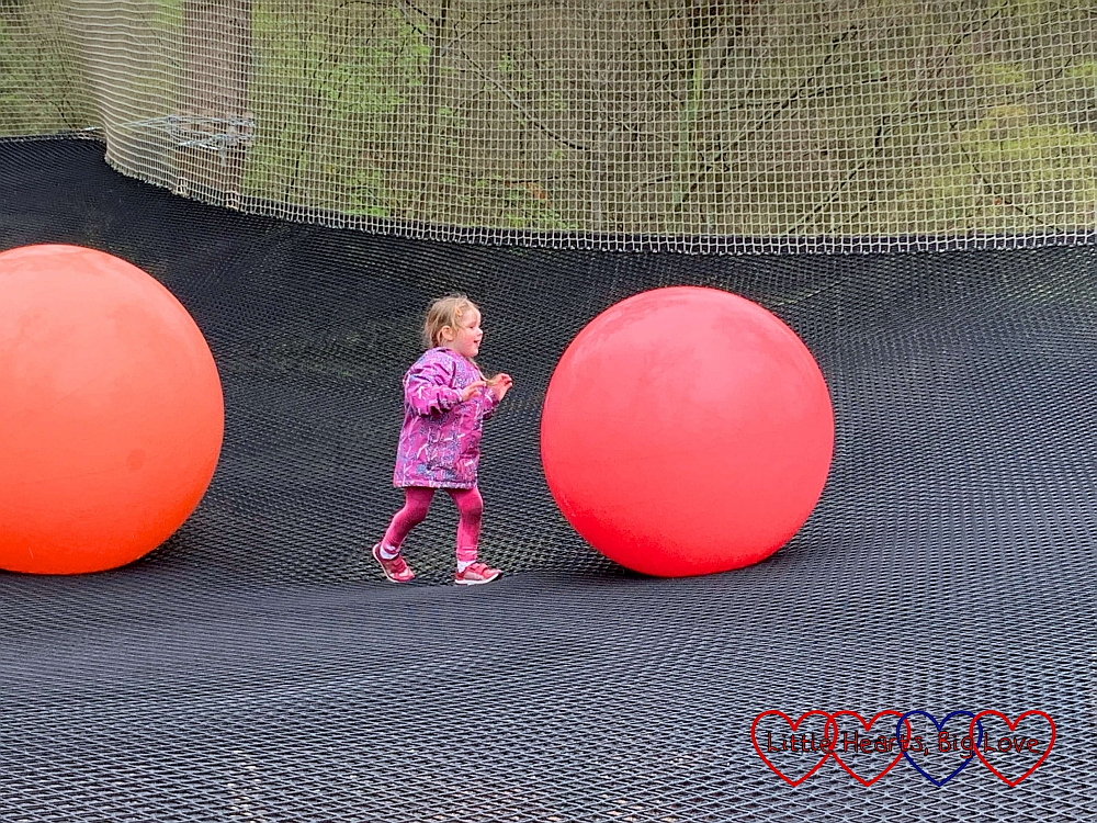Sophie pushing one of the giant inflatable balls across the nets