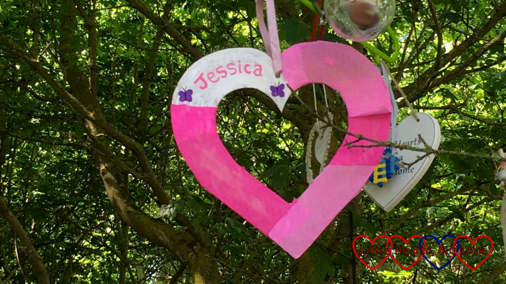"A pink and white heart with ""Jessica"" written on it hanging in a tree"