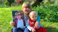 Sophie and Thomas sitting in Grandma's garden, with Sophie holding the picture of Jessica