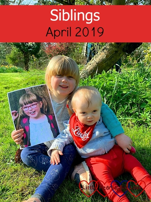 "Sophie and Thomas sitting in Grandma's garden, with Sophie holding the picture of Jessica - ""Siblings - April 2019"""