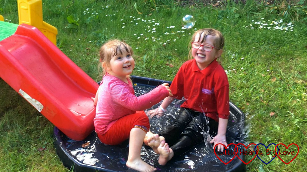 Jessica and Sophie sitting and splashing in a tuff tray full of water