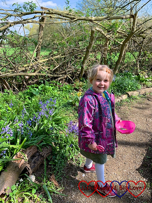 Sophie holding a bowl full of leaves standing next to a patch of bluebells