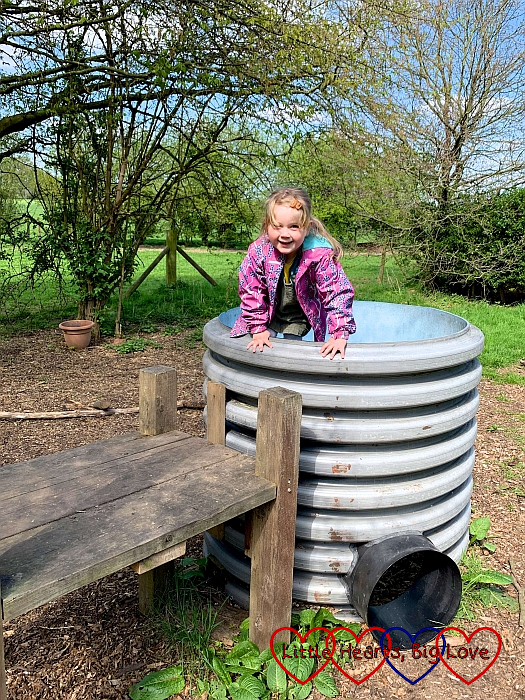 Sophie climbing into a big tub in the play area at Iver Environment Centre