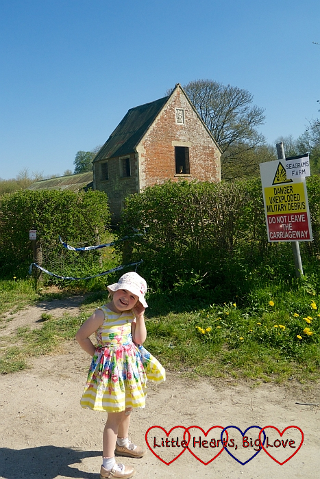 Sophie standing in front of an abandoned farmhouse in Imber village