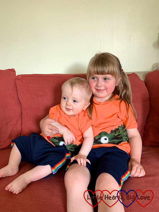 Sophie and Thomas wearing matching orange T-shirts and navy shorts with rainbow stripes
