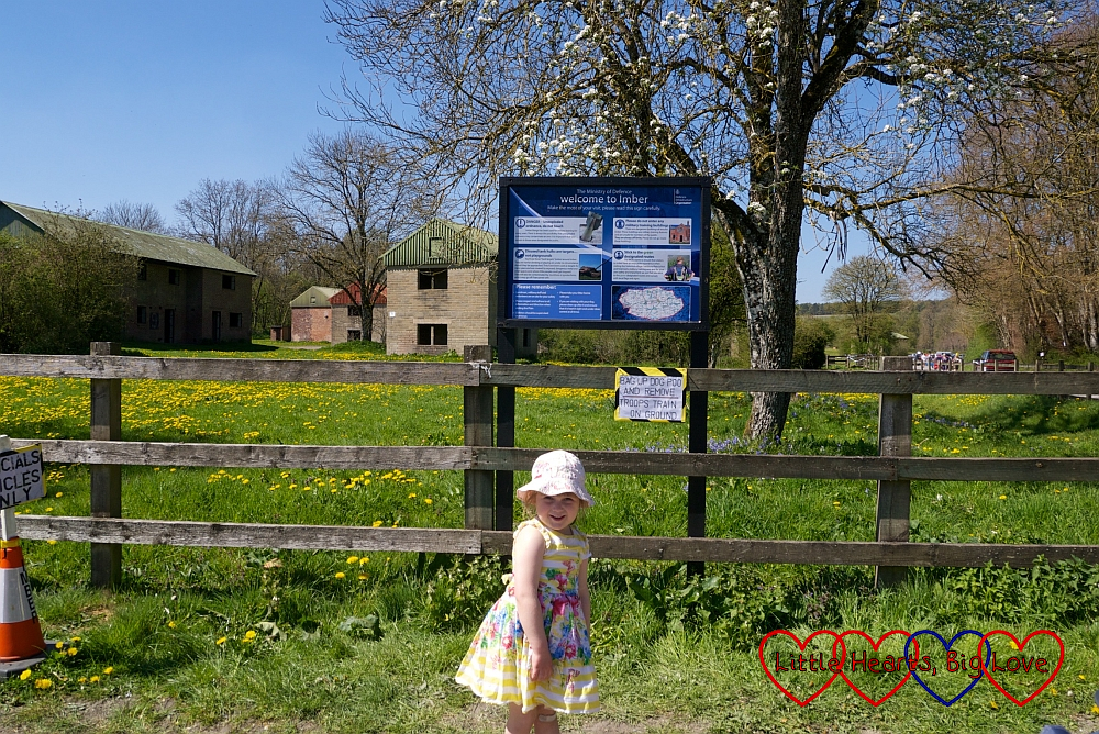 Sophie standing by the notice board near St Giles Church in Imber with the military mock-up buildings in the background
