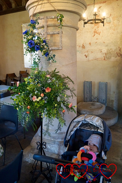 Thomas in his buggy next to one of the floral decorations in Imber church