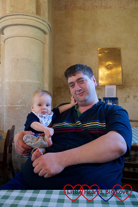 Hubby holding Thomas sitting inside St Giles Church, Imber
