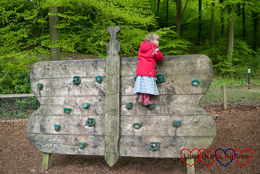 Sophie climbing a wooden butterfly