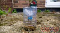 A rain gauge made from a plastic bottle outside in the garden