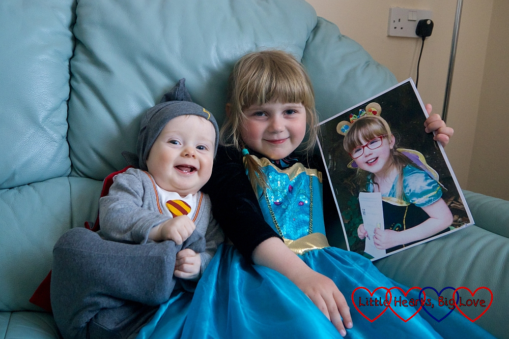 Thomas in a Harry Potter sleepsuit and Sophie in a princess dress holding a picture of Jessica in a princess dress