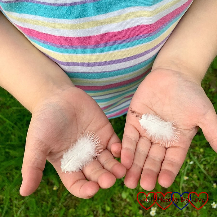 Sophie holding two white feathers