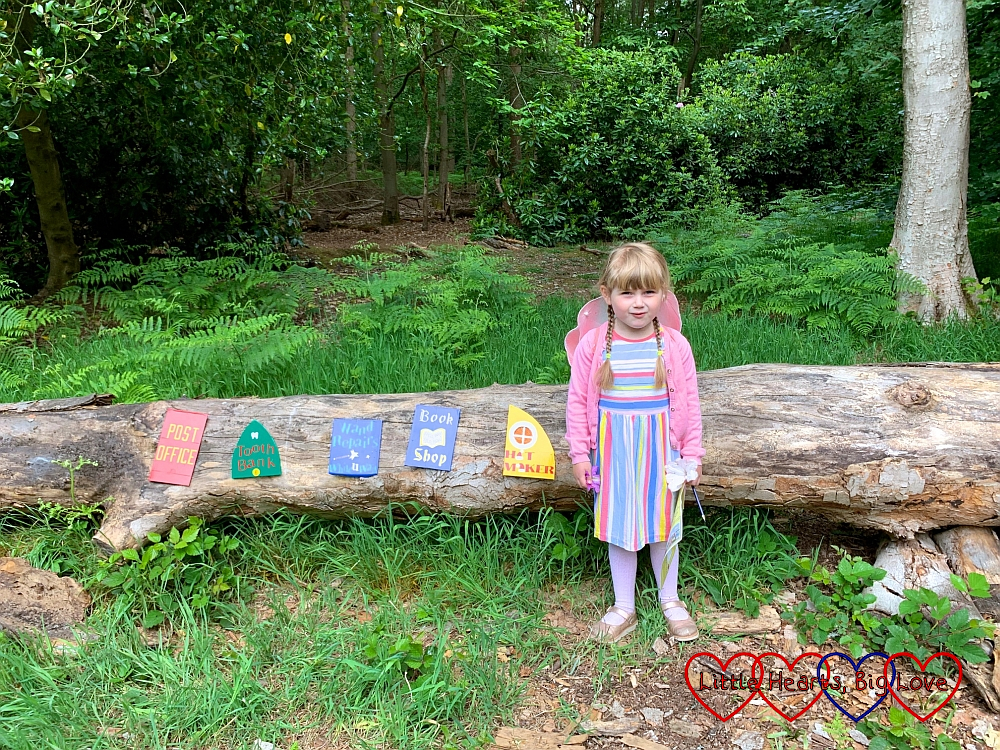 Sophie at the fairy village with little doors on a log