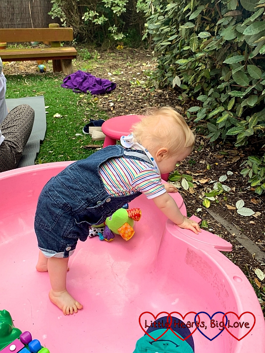 Thomas standing up in an empty paddling pool