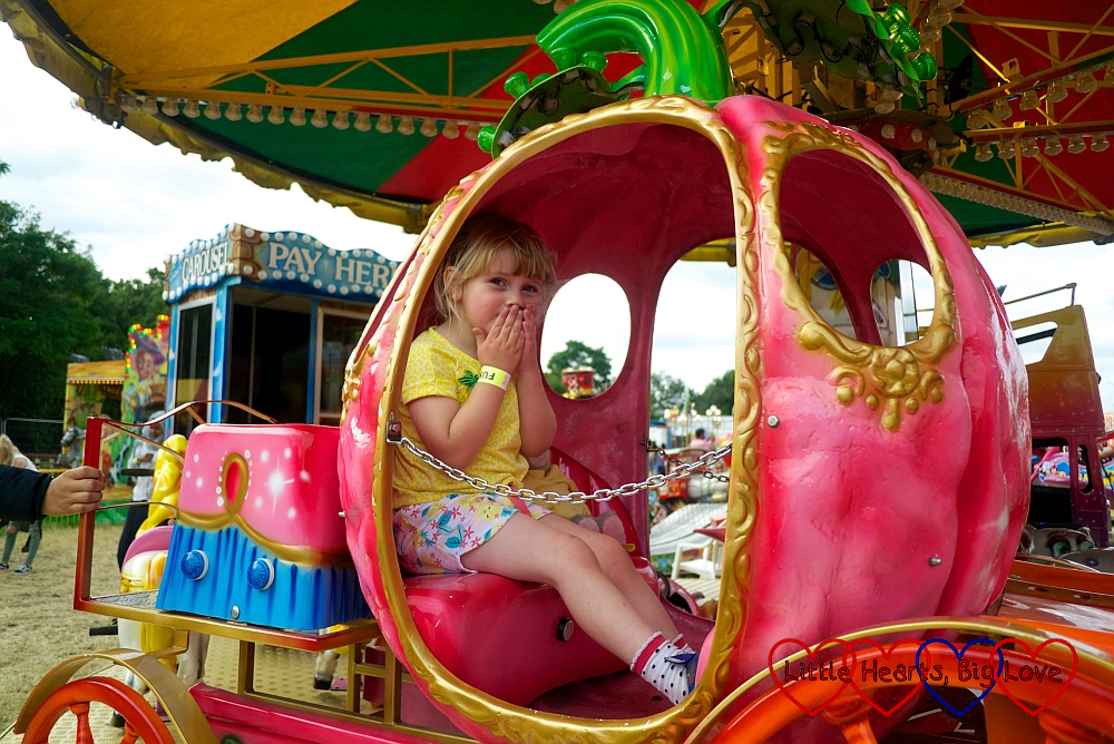 Sophie sitting in a pink carriage on the carousel