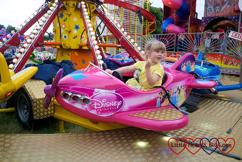 Sophie riding in a pink aeroplane at the fun fair