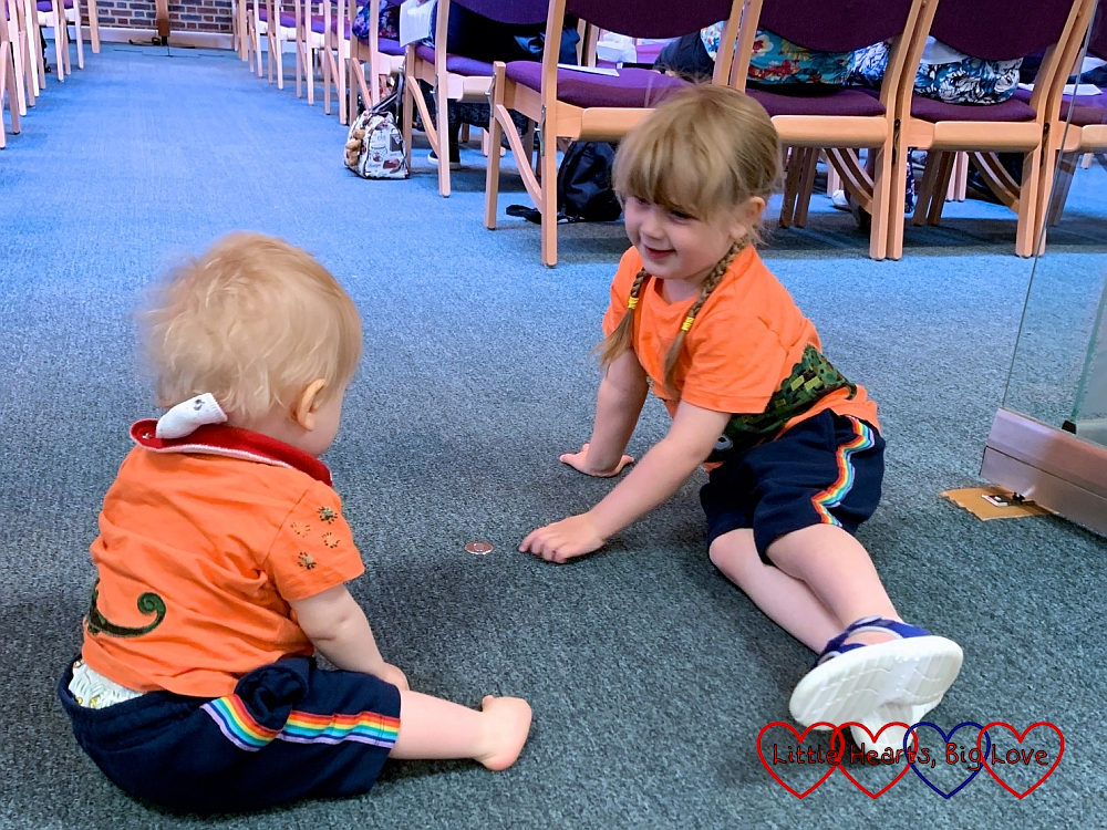 Sophie and Thomas sitting on the floor at church wearing matching orange T-shirts and navy blue shorts